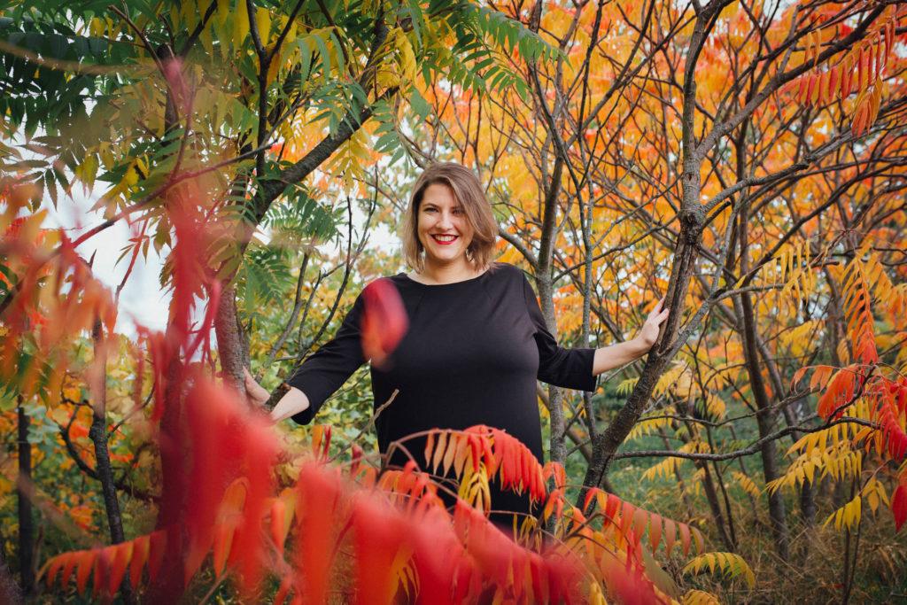 Sarah Schäfer steht inmitten rot und gelb gefärbter Laubbäume und lacht in die Kamera